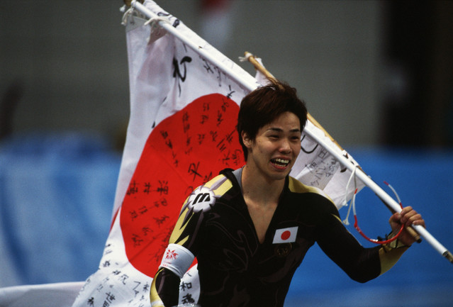 Japanese speed skater Hiroyasu Shimizu carries his countries flag after winning the gold medal in the men's 500m at M-Wave during the 1998 Winter Olympics. (Photo by © Wally McNamee/CORBIS/Corbis via Getty Images)